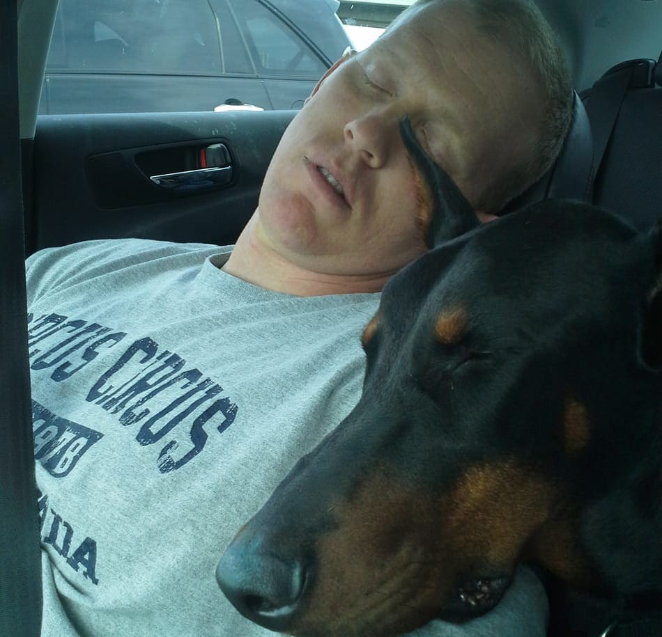 Me asleep in the car with my dobie Cooper.