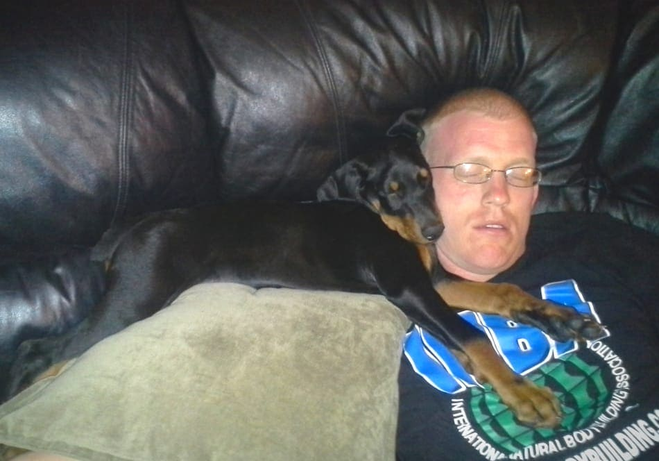Sleeping Doberman puppy with his owner.