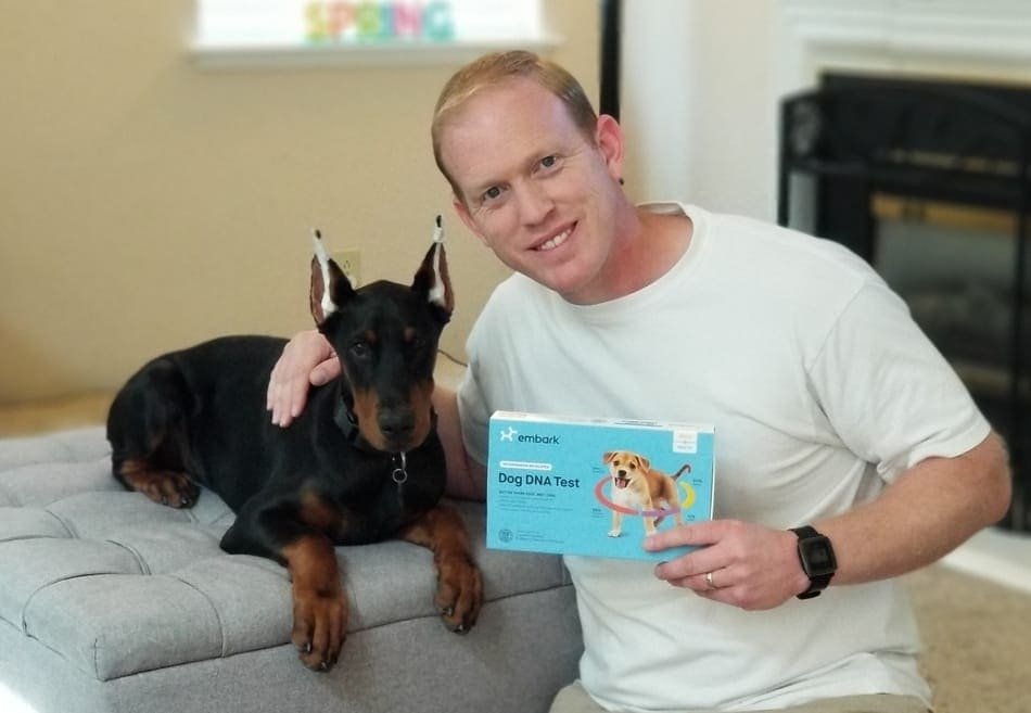 My Doberman Puppy Arlo and I holding my DNA test kit.
